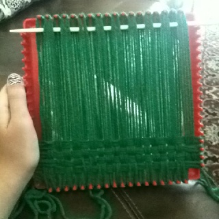 Weaving with yarn on a potholder loom. (Mrs. George)