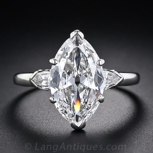 This superior and stunning diamond engagement ring sizzles with an absolutely clean, ice-white, old-cut marquise diamond weighing 3.39 carats. The stone was masterfully cut during the early-twentieth century and has the outline of a 4.50 carat diamond without sacrificing its inherent brilliance. The magnificent diamond is simply and elegantly presented in its original consummate Art Deco inspired mounting with a shield shape diamond enlivening each shoulder. Accompanied by a GIA Laboratory…