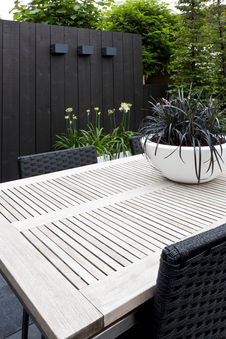 Black wall and white table interspersed with greenery, beautiful. Pinned to Garden Design by Darin Bradbury.