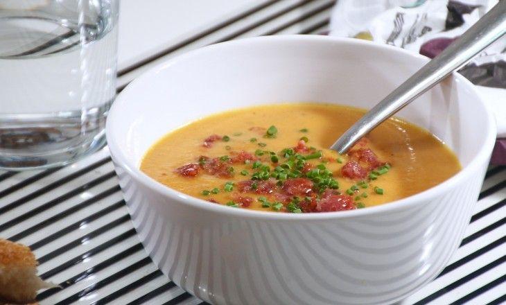Knallgul glad soppa med morötter, apelsin och brynt lök, smaksatt med ingefära, stjärnanis och lite chili, toppad med knaperstekt salsiccia och gräslök. L
