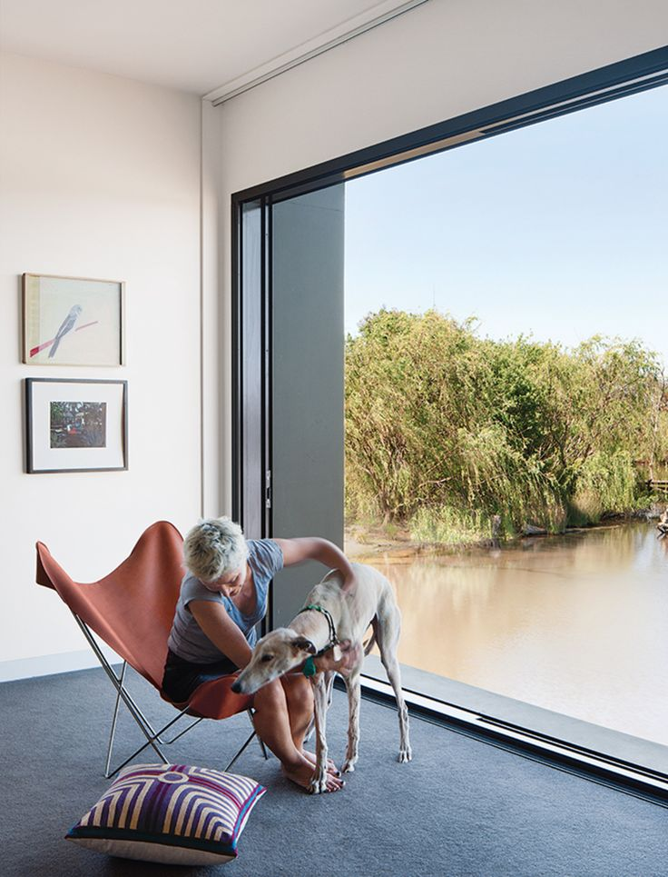 With a large glass door from Capral that opens completely to the elements, the master bedroom becomes part of the landscape. Imogen sits with Millie, one of the family's two greyhounds. The art is by Noel McKenna (top) and Ray Crooke; the butterfly chair cover was custom-made by a saddler.