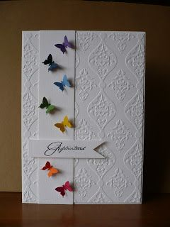 Tiny colorful butterflies on white embossed background