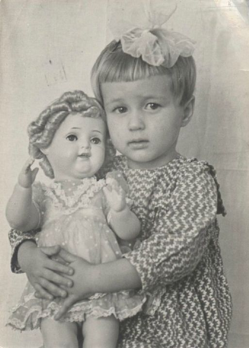 Vintage photo of little girl with her Shirley Temple doll, circa 1940 - 1950.