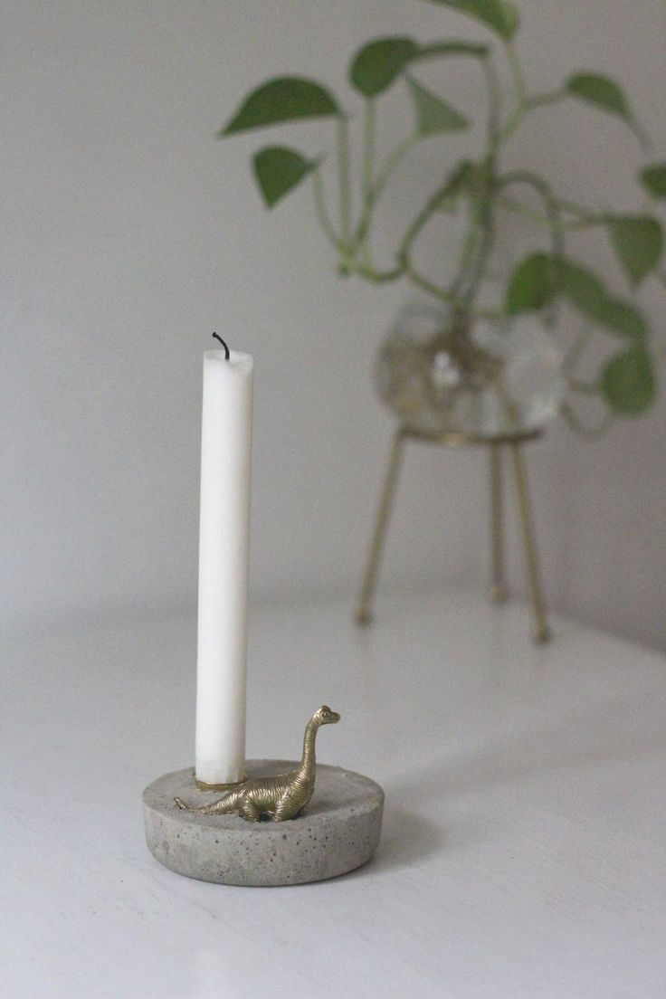 DIY concrete candle holder with golden dinosaur toy