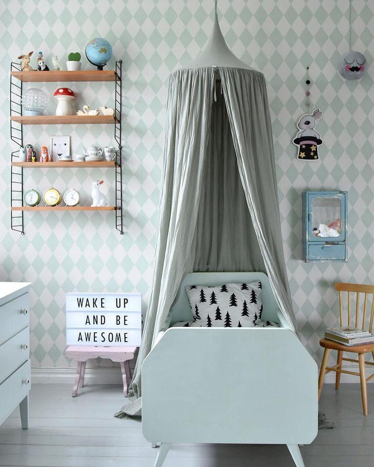 Łóżeczko z baldachimem na tle wzorzystej ściany w dziecięcym pokoju