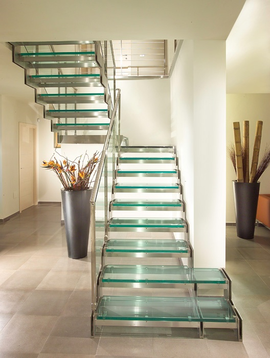 Staircase with modular stainless steel side structure and steps in float stratified glass and banister in stainless steel and stratified glass