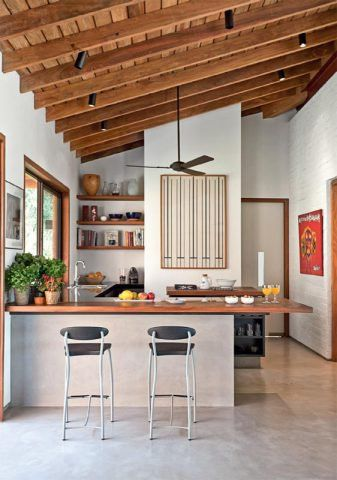 A bancada de cumaru divide a sala da pequena cozinha e atende também à mesa externa, ligada a este canto pela janela lateral. Ótima para refeições rápidas, sua base de alvenaria ainda armazena louças e utensílios. Projeto de Studio Casa 4.