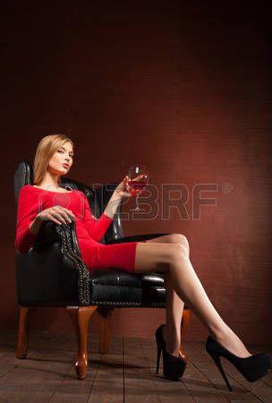 Portrait d'un mod�le � la mode superbe assis dans un fauteuil avec un verre de vin. Affaires, femme d'affaires �l�gante. Int�rieur, meubles. photo