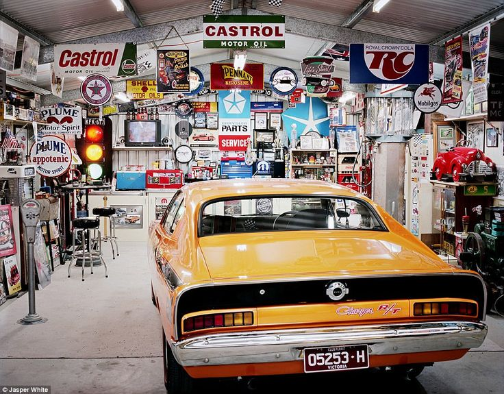 Pit stop: This man cave features a a classic yellow Chrysler Valiant Charger, before a variety of vintage signs including Castrol Motor Old, Plume Motor Spirit and Mobilgas