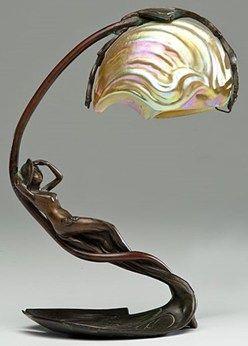 Lámpara de mesa de estilo Art Nouveau Nautilus por C. Bonnefond , francés, finales de los 19 o principios del siglo 20 . Una lámpara art nouveau con una base de bronce de una ninfa recostada en un cojín de lirio y una sombra iridiscente en la forma de una concha de nautilus , la base firmó C. Bonnefond .