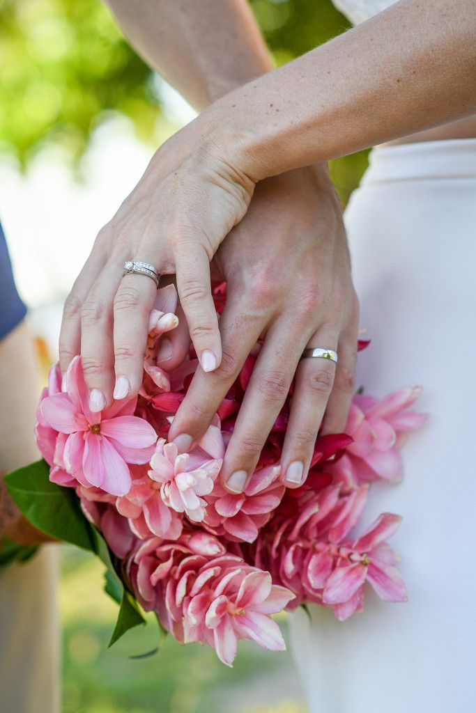 Bride and groom wedding silver rings by the tropical pink flower bouquet. In Fiji by Anais Photography.