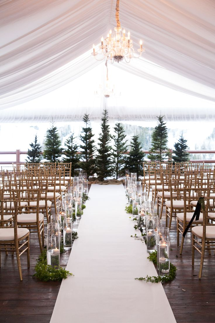 Tented wedding ceremony with evergreen trees and candles | Winter wedding at Stein Eriksen Lodge in Deer Valley, Utah | Black tie wedding, under a soft fabric tent, with glowing candles, gold Chivari chairs, lush white flowers, evergreens trees and branches, and black accents | Planning: Soiree Productions | Flowers: Decoration Inc. | Photography: Melissa Kelsey Photography | http://www.melissakelseyphotography.com