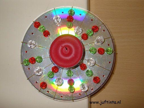 waxinelichtje op cd Teken eerst op de achterkant van de cd op gelijkmatige afstand waar de draadjes moeten komen. (zie foto hieronder). Zorg voor een even aantal. In dit geval zijn het er 16, zodat er 8 draadjes gespannen worden. Neem een stuk draad, rijg hier een aantal kralen op en span deze over de cd. Aan de achterkant maak je het draadje nu met plakbandjes vast. Zorg ervoor dat er in het midden geen kralen zitten, omdat daar het waxinelichtje moet komen.