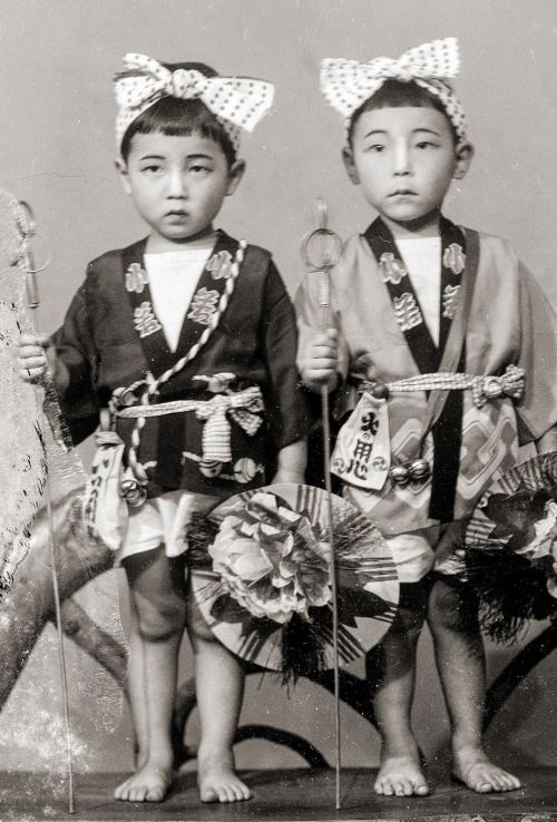 Vintage portrait of two Japanese boys in traditional happi coats and headbands (with bows). They are also holding some kind of sticks and another item that looks like a giant flower - not sure what this is, but maybe related to a local festival? This photo is from a found wooden box of vintage Japanese portraits that appear to have been taken by a portrait photographer, possibly between the 1930s to 1950s in Japan.  and image via Vintage Japan-esque on Flickr