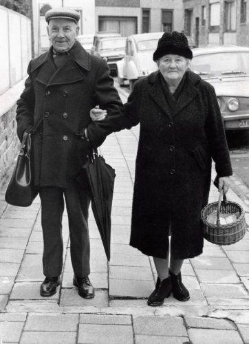 Bejaarde man en vrouw lopen gearmd, met mandje, tas en paraplu, op een trottoir. Nederland, plaats onbekend, 1976