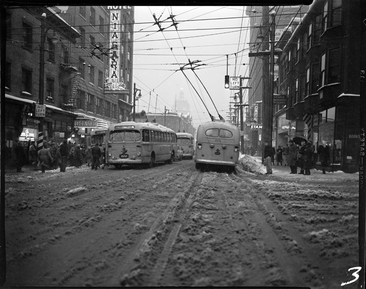 B.C. Electric buses at Pender Street at Seymour Street in the snow VPL Accession Number: 82437 Date: January 26, 1954 Photographer/Studio: Artray Content: Photo series