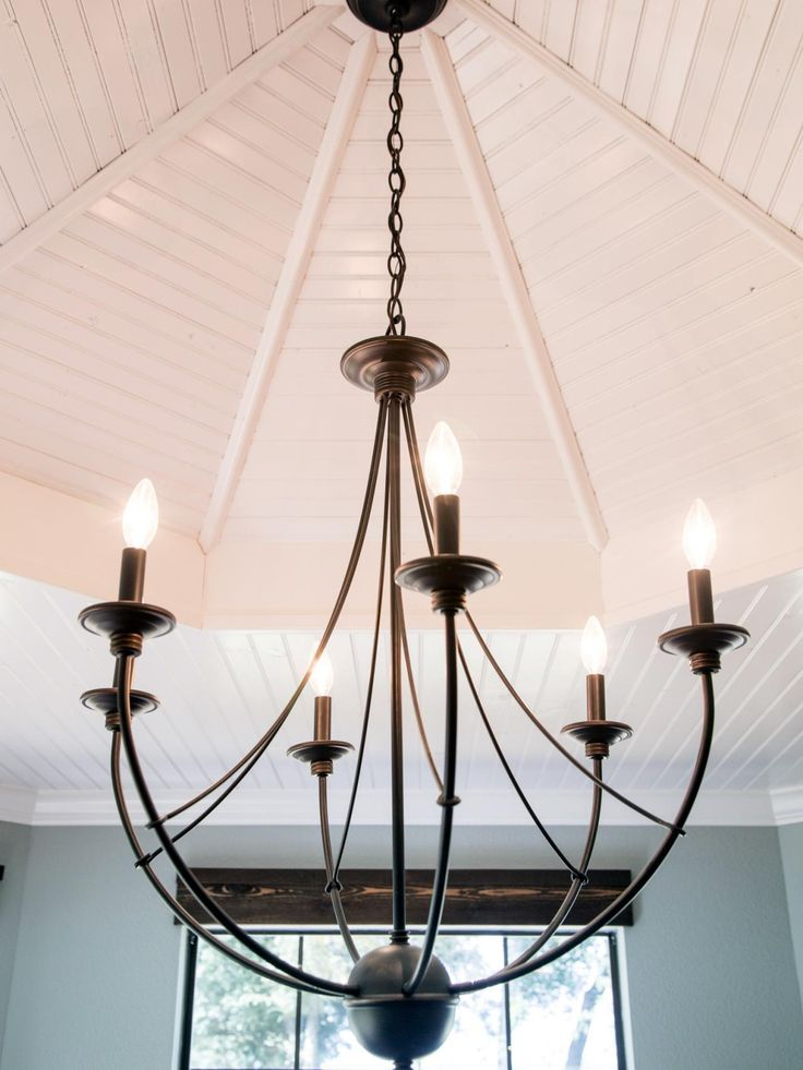 In The Dining Room A Brushed Bronze Chandelier Hangs From Freshly Painted Cove Ceiling