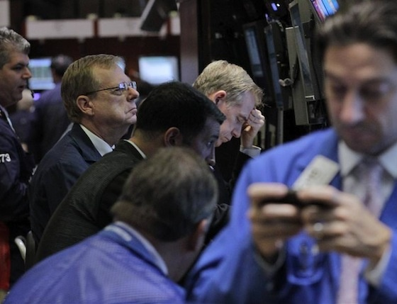 Traders work as a television screen shows U.S. Federal Reserve Chairman Ben Bernanke, on the floor of the New York Stock Exchange