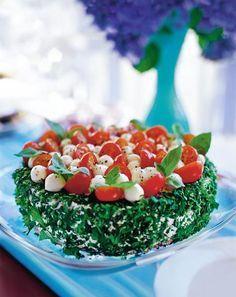 Etsinnässä ihana kasvisvoileipäkakku? Kaunis tomaatti-mozzarellakakku on silmänilo ja juhlapöydän mehevin herkku, jossa maistuvat tomaatti, mozzarella ja basilika.