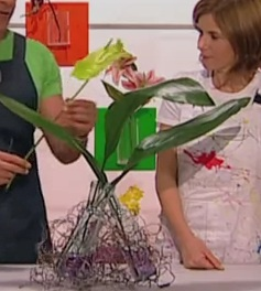 Fiori e trasparenze.  Questa idea consiste nel creare un vaso di fiori utilizzando materiali ricicalti. In questa soluzione vengono riciclati i fili di ferro e le bottiglie in vetro. La soluzione proposta può essere sviluppata anche con l'utilizzo di bottiglie in plastica.