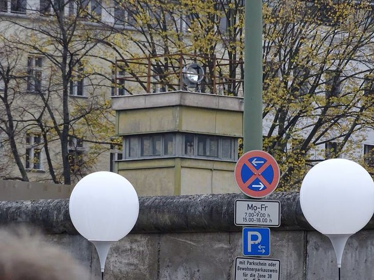 Balloons in front of a small area of the Berlin Wall which has been preserved, complete with watchtower and barbed wire
