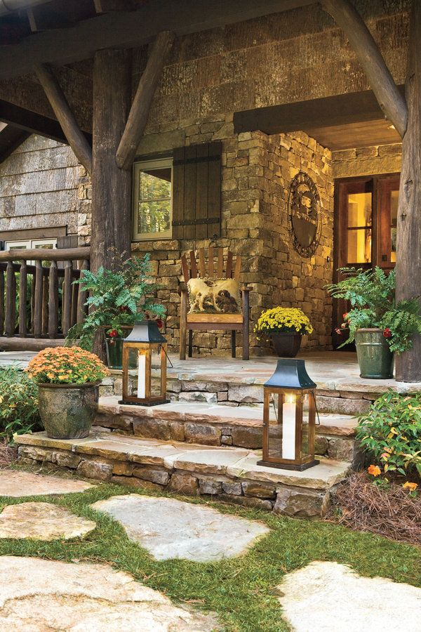 Randomly placed stepping-stones crafted from local granite lead to this front porch's wide steps. Hand-hewn posts and railings, along with graceful brackets, are crafted from regionally harvested locust wood to further enhance this cottage's connection to the land. Local fieldstone clads the porch walls.  Tour this Mountain Cottage