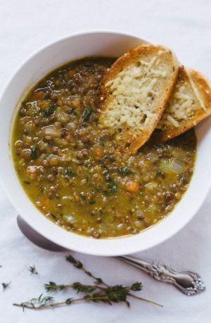 SOUPE DE LENTILLES (Pour 4 P : 1 jarret de porc, 4 gousses d'ail, 1 oignon, 4 carottes, 4 tiges de céleri, 3 c à s d'huile d'olive, 3 tasse de lentilles, 1 c à s de cumin,  ½ L de bouillon de légumes,  1 feuille de laurier, 2 brins de thym, sel et poivre au goût)
