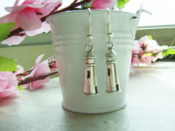 With seagulls overhead, the lighthouse rises up above the jagged rocks and coastline. Pretty lighthouse earrings...