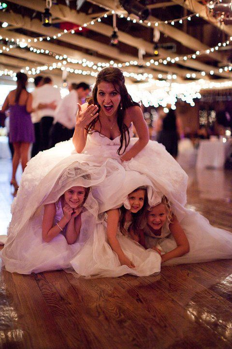 adorable flower girls hiding under dress unique wedding day photo ideas bride with flower girls wedding party blog