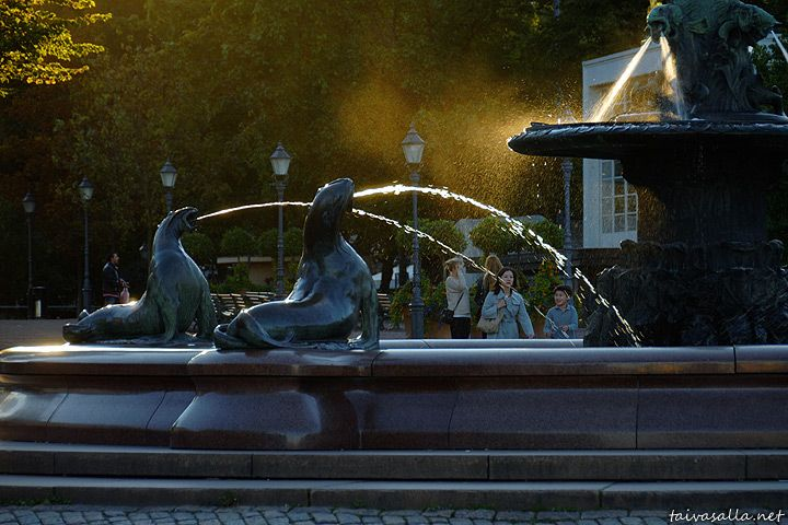 taivasalla.net - Under the Open Sky - September 2011, Helsinki: Water spouts of the Havis Amanda statue lit by bright evening sunshine. Picture taken from the Market Square towards the Esplanade Park.