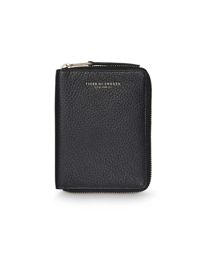 Madesimo wallet-Women's wallet in soft napa leather. All-round zip with leather strap on puller. Eight credit card slots. Embossed Tiger of Sweden logo. Size: 10.5 x 13.5 cm.