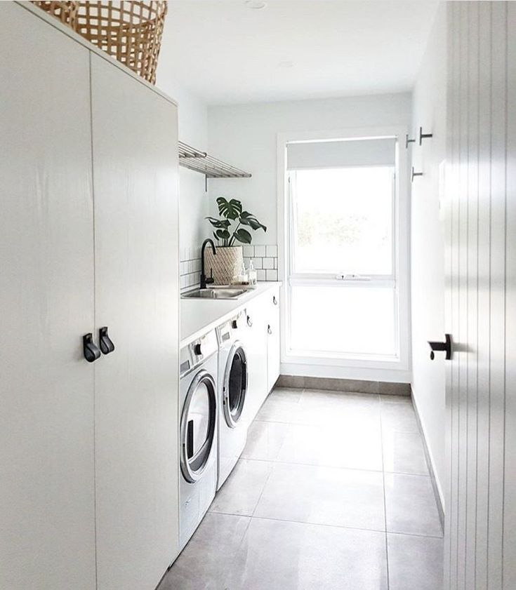 Light, bright and airy laundry with white cabinetry, black leather pull handles and black tap.