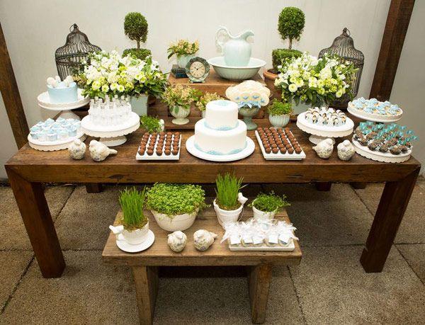 Organização linda de mesa: bolo no meio, brigadeiros dos lados, dois arranjos pequenos atrás e mais docinhos na frente, incluindo as lembrancinhas.