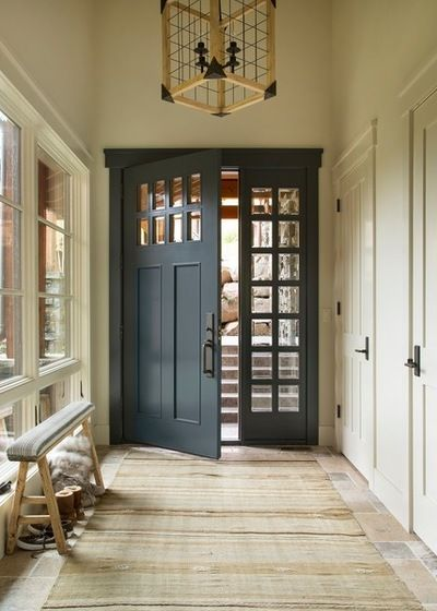 Beautiful entryway featuring an iron pendant and a gorgeous front door painted…