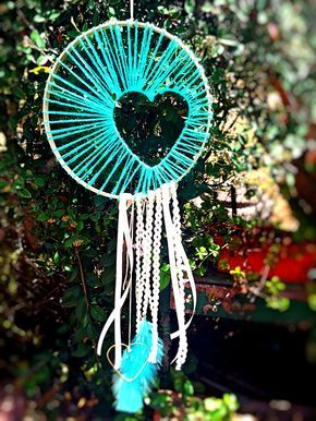 ATRAPASUEÑOS CORAZÓN DOBLE AQUAMARINE  Materiales: Madera, lana verde aguamarina, cintas ric rac, cinta de raso fina, mini corazón dorado y pluma verde aguamarina Tamaño: 25 cm diámetro