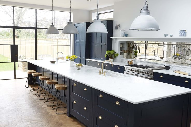 Stunning kitchen by Blakes London. Love the white worktops, navy cabinets, wood flooring and brass hardware