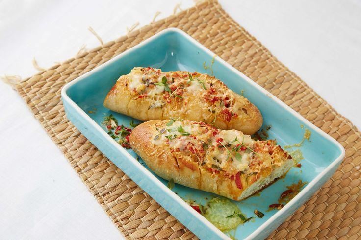 Oppskrift på en nydelig baguett stekt i ovn, snittet og fylt med chili - og hvitløkssmør, pepperoni og drysset med saftig ost og friske urter. Dette er virkelig kosemat med stor K!