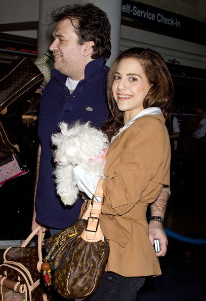 Brittany Murphy Photos - Brittany Murphy and husband Simon Monjack get hammy for the cameras with their pup as they check in for their departing flight at Los Angeles International Airport (LAX). In addition to their furry friend the couple carts a mountain of luggage. - Brittany Murphy Photos - 79 of 637