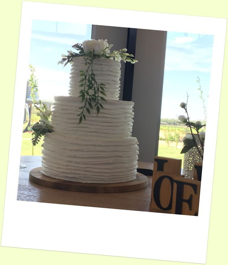 White frosted - classic 3 tier wedding cake. Top tier is gluten free.   All 3 tiers are traditional vanilla cake with white chocolate ganache and raspberry coulis