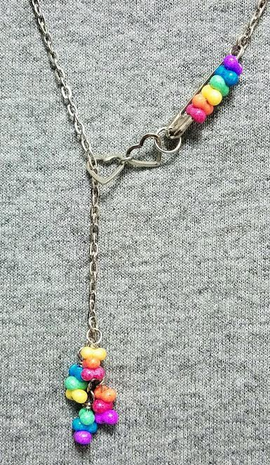 Rainbow Lariat necklace is adjustable up to 24. Silver chain, silver safety pin, and two silver heart connectors with rainbow colored stone beads on both the safety pin and dangles at the end of the necklace.  All proceeds benefit the Trevor Project for LGBTQIA youth! http://www.thetrevorproject.org/  Founded in 1998 by the creators of the Academy Award®-winning short film TREVOR, The Trevor Project is the leading national organization providing crisis intervention and suicide ...