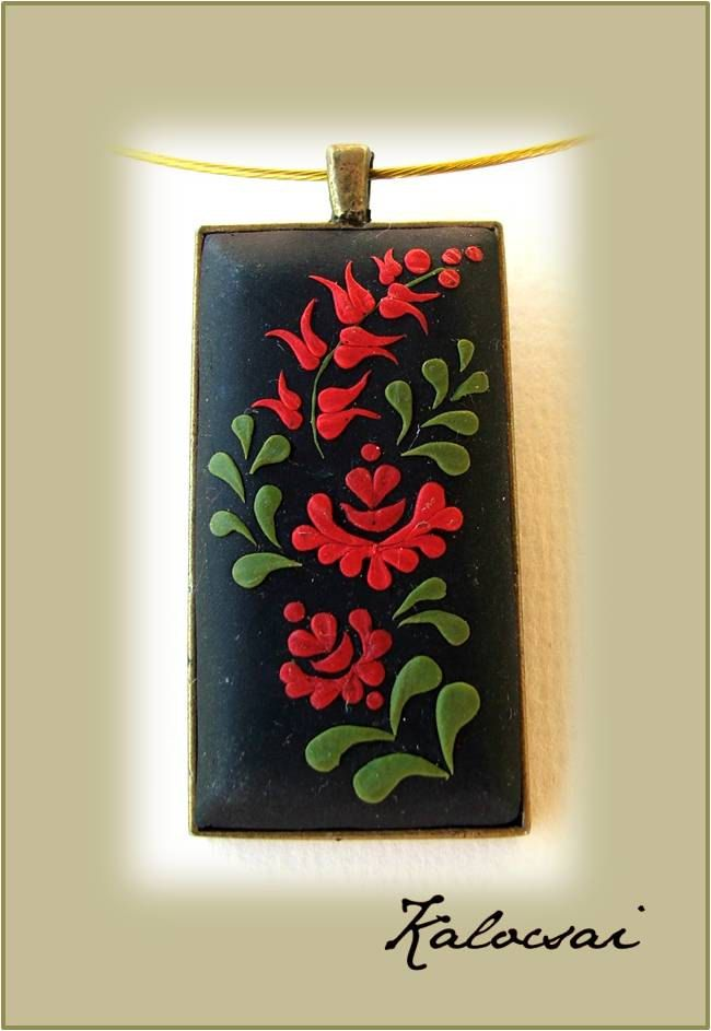 This is a unique, handmade, polymer clay pendant with Hungarian folk motifs in romantic style.  The base of the pendant antique bronze color copper alloy.  Inlays and decorations are made of polymer clay.    Sizes:  height: 5.2 cm / 2.04 inch  width: 2.7 cm / 1.06 inch    The method is known as appliqued technique. Using tiny pieces of clays and a sharp needle.  The pendant includes Steel Wire Necklace Cord, with Alloy Clasp.  The pendant is Wear-resisting, and Colorfast.    They ar...