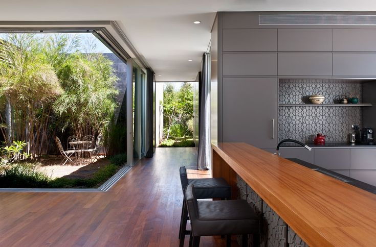 A simple breakfast bar area gets light and air from surrounding windows while an outdoor dining set sits just beyond on a small patio nook.