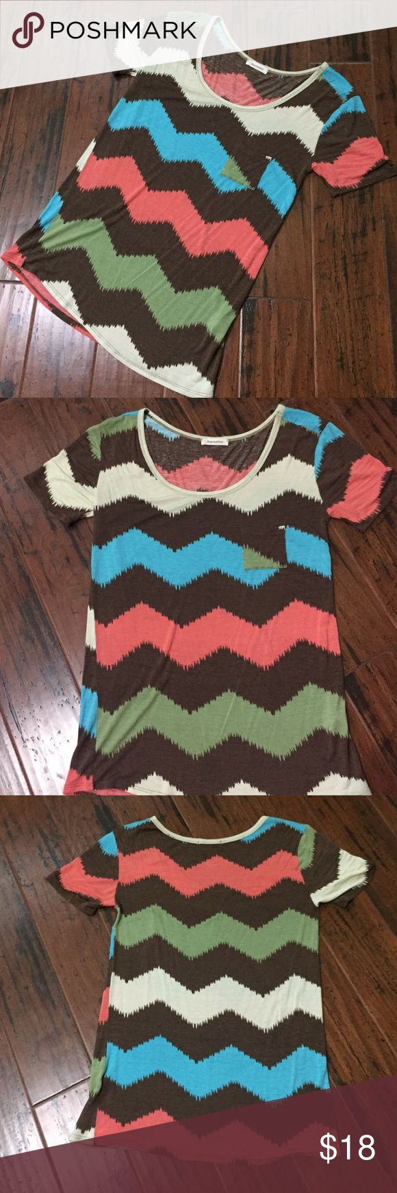 Chevron pocket tee NWOT Very cute chevron tee with pocket.  Brand is fascination but purchased through filly flair.  Love it but unfortunately not a lot of boutiques sale stuff that fit us petite girls and this was just too big for me. Tops Tees - Short Sleeve