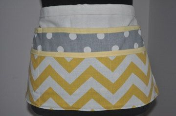 I love this color combination! This chevron utility apron is perfect for a busy day! Teacher aprons are so helpful in the classroom!  Remember that old commercial jingle-Strong enough for a man, made for a woman? That is exactly what this womens vendor apron is. It is sturdy and stylish, made from denim and duck cloth. This great craft fair apron can stand up to a lot and just be hosed off at the end of the day. This yellow chevron apron is great for anything, the gray polka dot apron is 22…