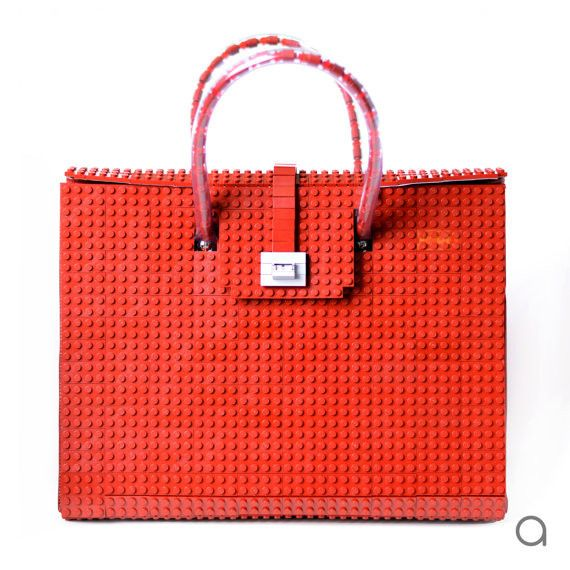 This dark red AGABAG tote is a chic choice for everyday use. It is handcrafted with LEGO bricks. Its interior is generously proportioned to fit all of your daily essentials, including an iPad and work documents.