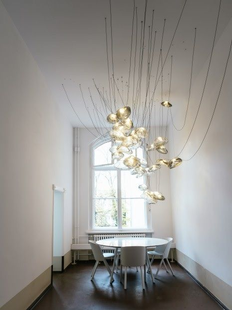 A clusters of bocci 73 pendants by omer arbel and this dining chairs by stefan diaz are surrounded by low slung contrast painted walls