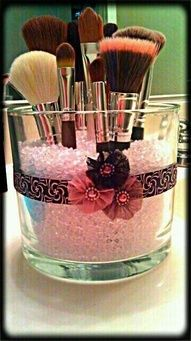Make up brush holder. Empty candle holder glass, filled with rice, with ribbon on side for decoration