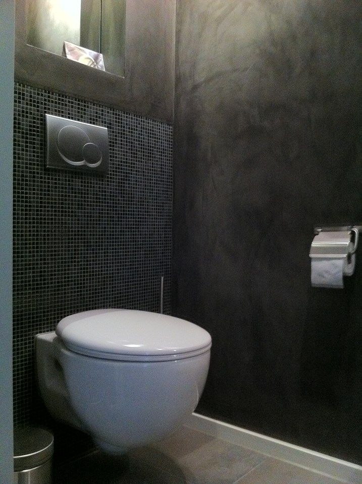 Stuc Deco toilet met kleine wandtegels, pleisterwerk en vloertegels.
