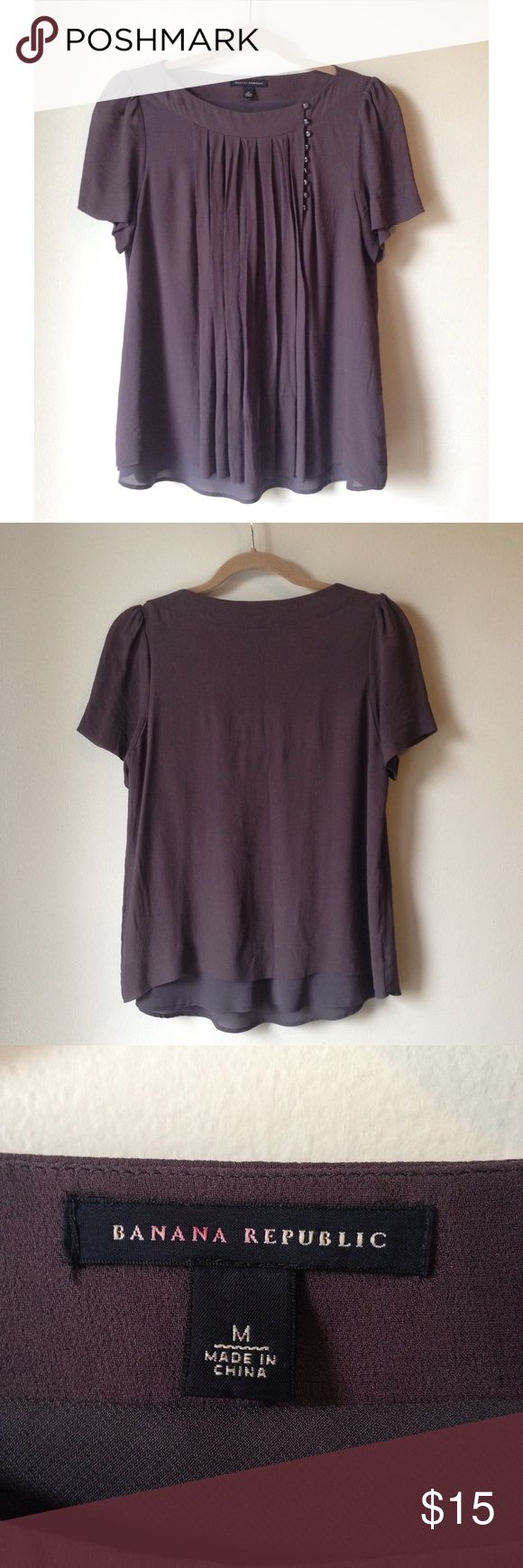 // 100% SILK BANANA REPUBLIC Pleated Silk Top // 100% Silk top by Banana Republic. This adorable flowy shirt has pleating and button details in front. Very cute short sleeves. Sheer material peeks out from the bottom.  Adorable top, can even be used as maternity top.   • Size Medium • Color is a grayish purple Banana Republic Tops Blouses
