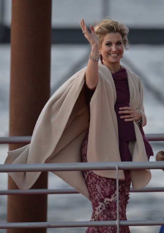 Queen Maxima of the Netherlands waves prior to take part in a water pageant on the river IJ in Amsterdam on the day of the new King's investiture